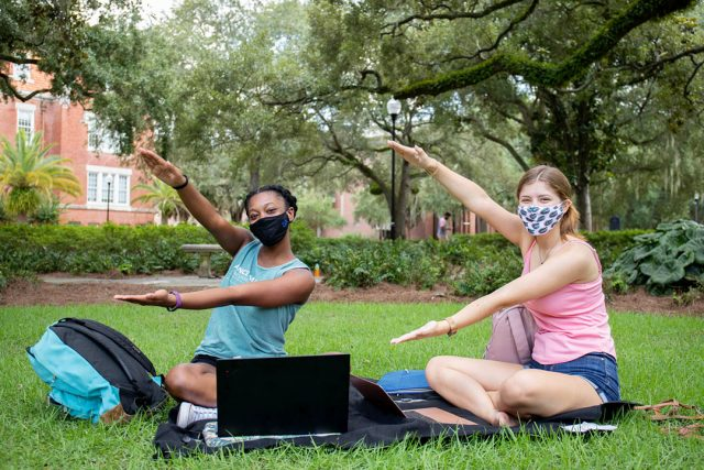 Two students sitting on the lawn, wearinging masks and doing the Gator Chomp
