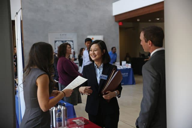 a group of 3 people at the Just in Time career fair