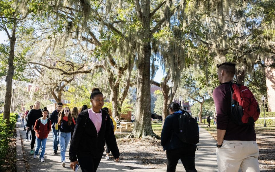 Campus scene of multiple students walking along a sidewalk