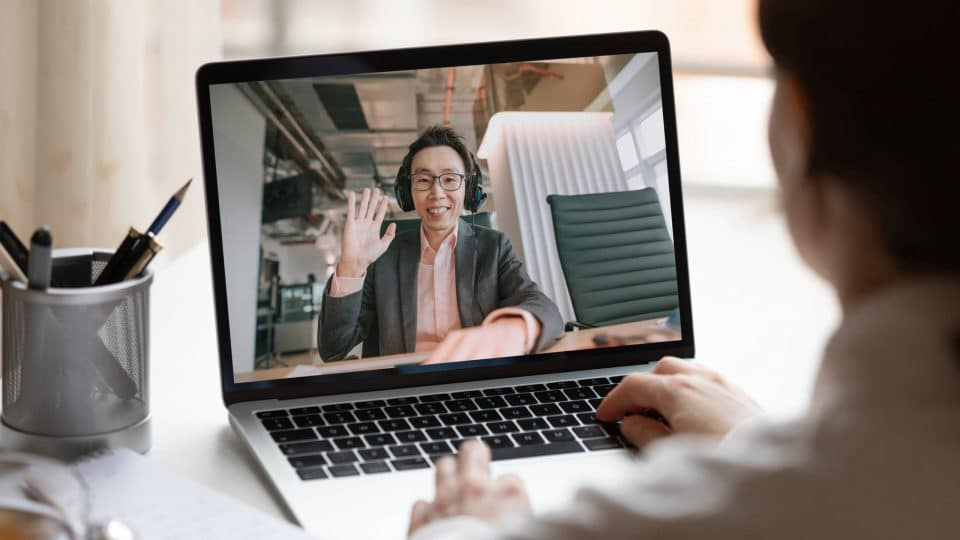 Person using a laptop with a screen showing someone in a virtual meeting