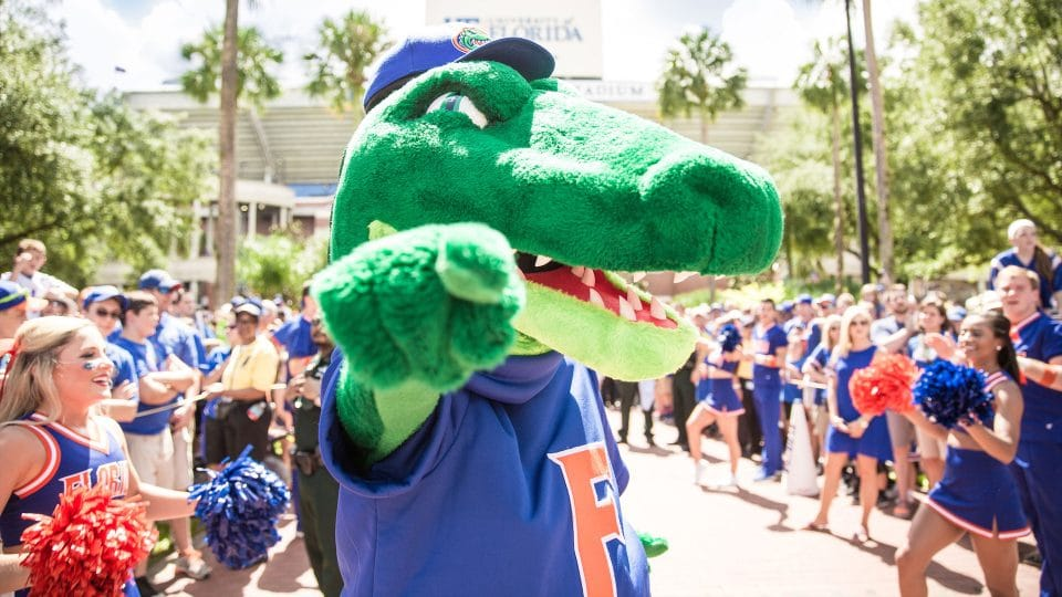 Albert Gator points into the camera while cheerleaders and fans assemble for a football game day