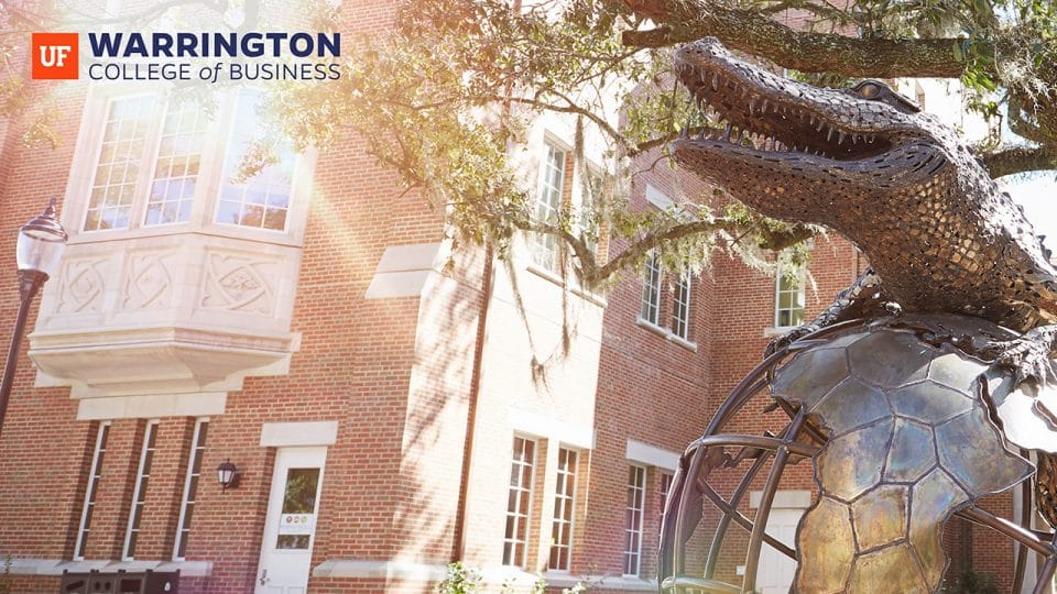 Photo of the Gator Ubiquity Statue with Heavener Hall in the background and the Warrington College of Business logo in the upper left