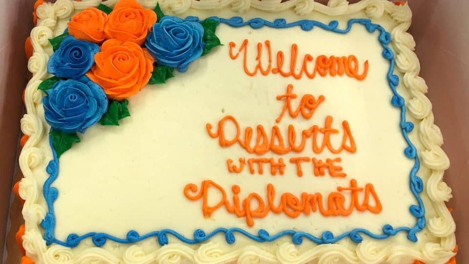 A cake decorated in orange and blue which reads Welcome to Desserts with the Diplomats