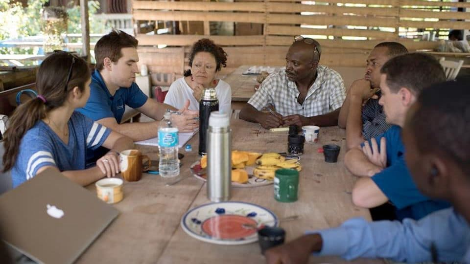 UF students sit at a table with locals in Haiti