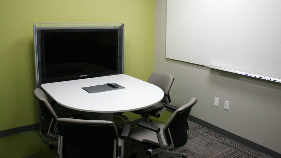 A room with a small table, a large monitor and a whiteboard