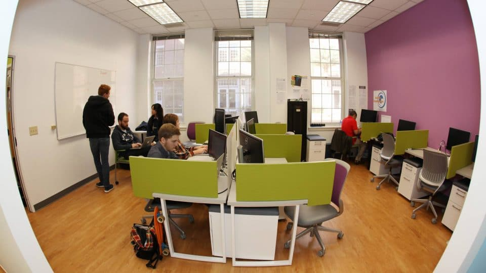 Students work at stations with computers in the incubator for the Entrepreneurship and Innovation Center
