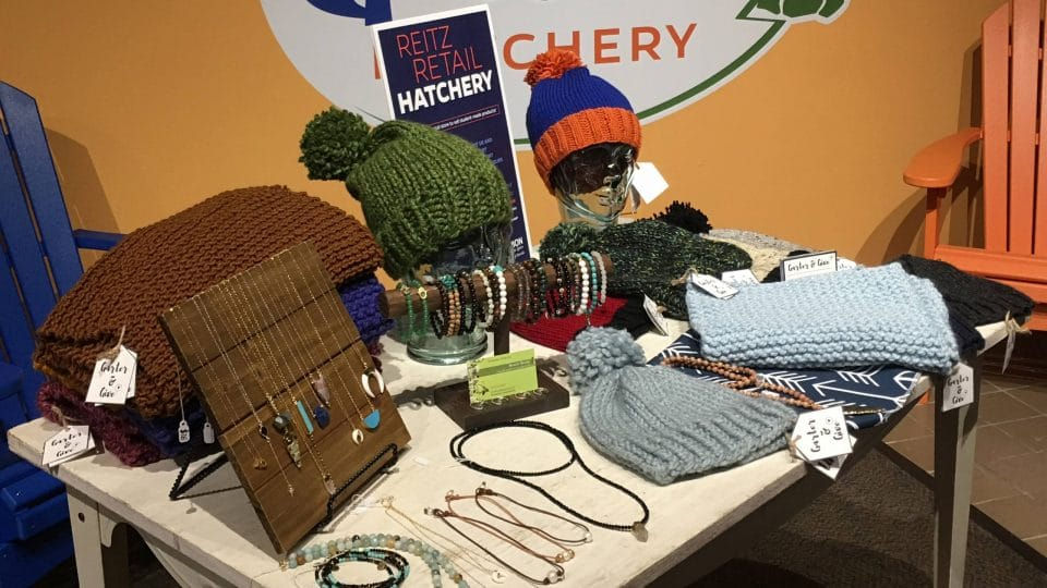 A table displaying knitted products and jewelry at the Retail Gator Hatchery