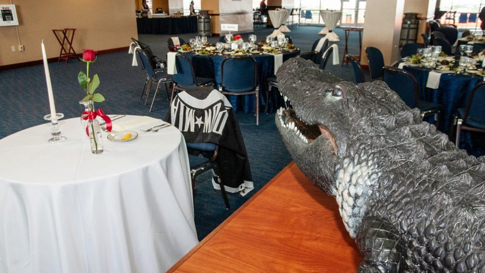 A Gator statue overlooks dining tables, one chair has a POW-MIA flag draped over it