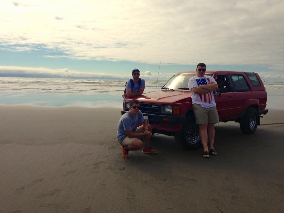 Three FLA students on the Pacific Ocean beach with a red vehicle
