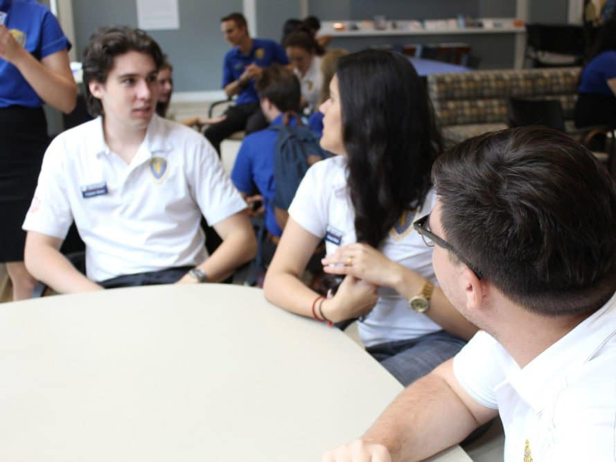 Three FLA students in discussion around a table