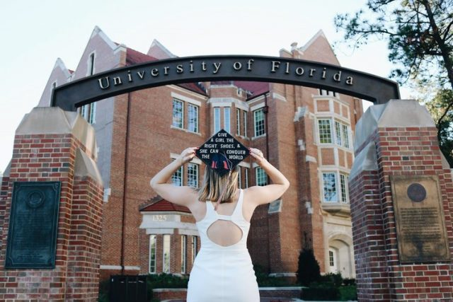 Graduate with decorated mortar board looks on at the University of Florida gateway with Heavener Hall in the background