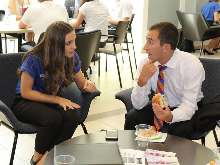 Two students converse over lunch
