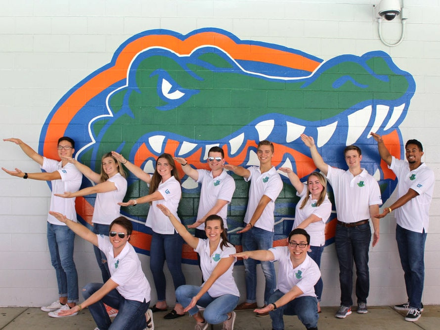 Group of HLC students Gator Chomp in front of a Gator logo on a wall