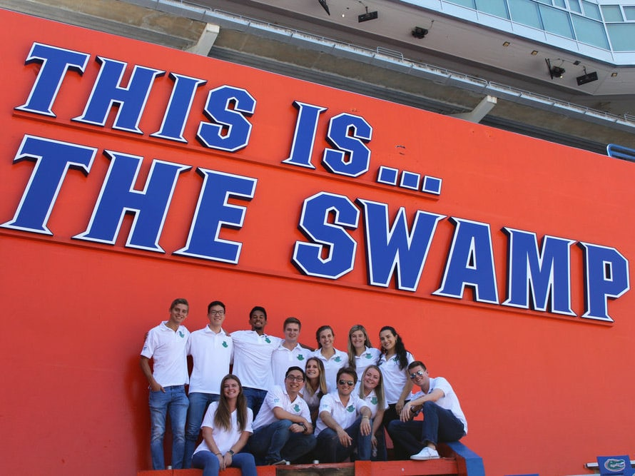 Group of HLC students in the Ben Hill Griffith Stadium under This is... the Swamp text on wall