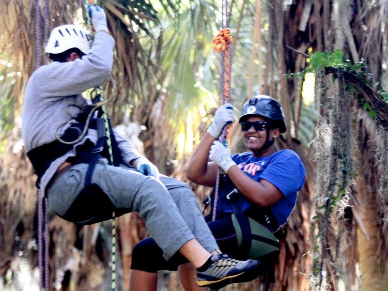 Two MSE students hang from climbing ropes in the trees