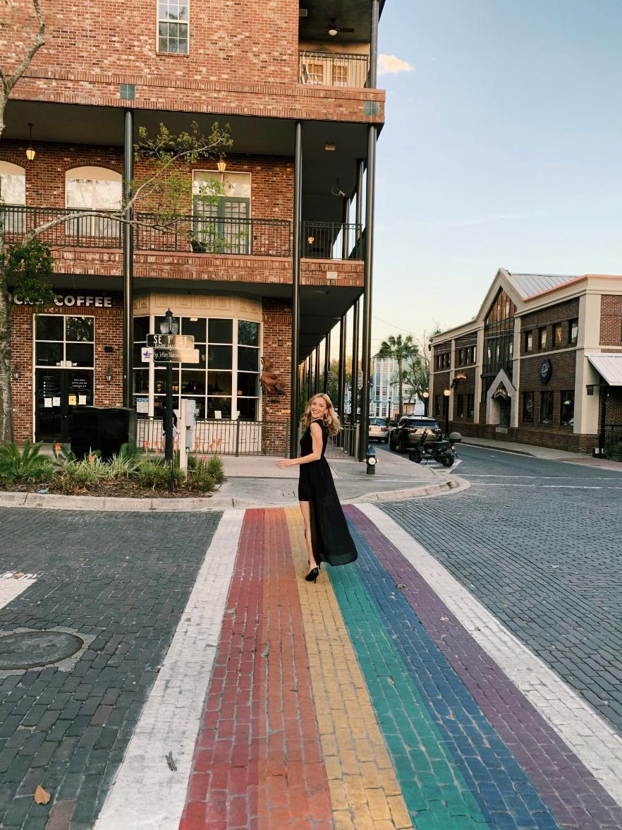 Person in an evening dress looks over her shoulder as she walks on the rainbow colored crosswalk, downtown Gainesville