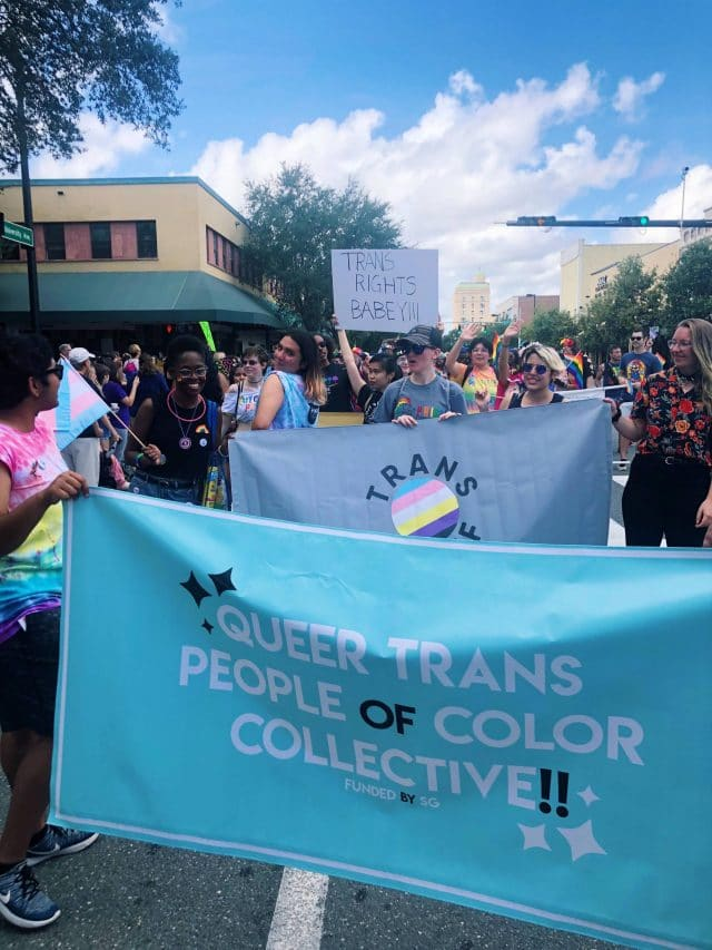 Students gather with banners at a Pride Parade in Gainesville