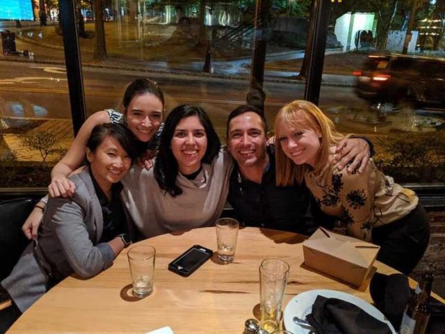 Five people smile for the picture while gathered around a table in the evening with a street outside the window behind them