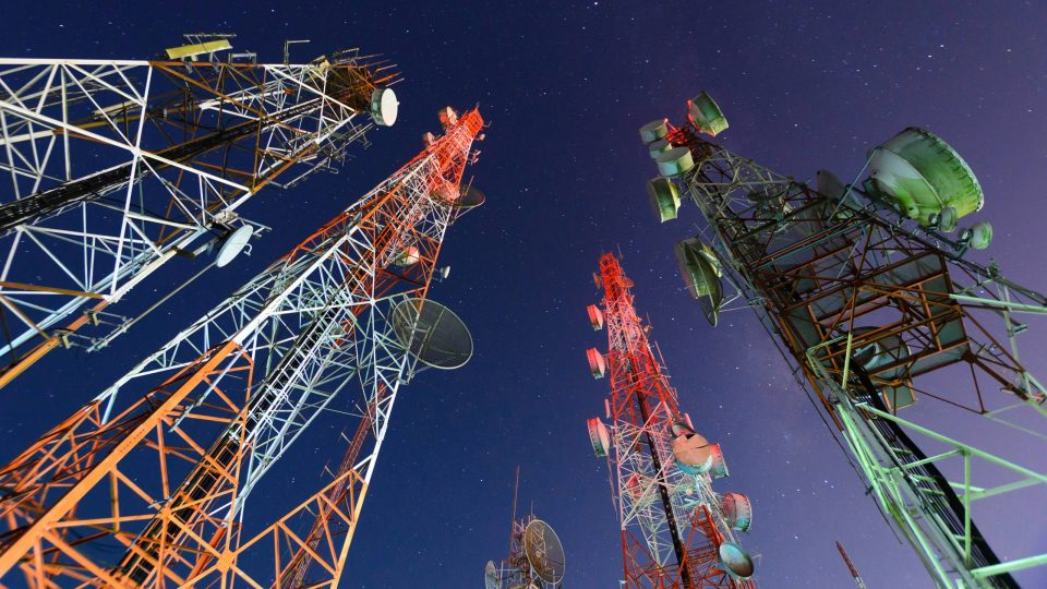 Five telecommunication towers from the ground looking up into the night sky