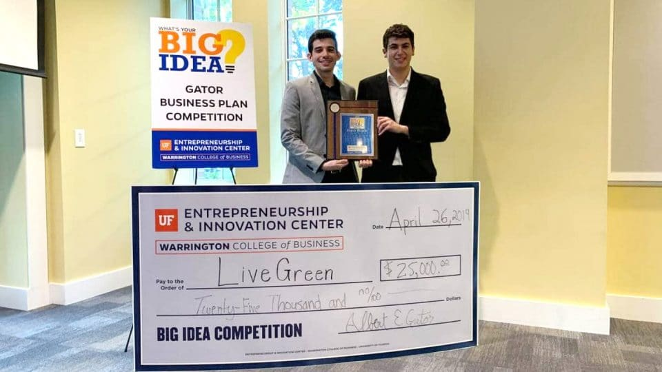 Two students accept the award and $25,000 check for the Big Idea Gator Business Competition Plan