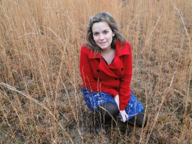 Camila Pazos kneeling in tall, wild grass