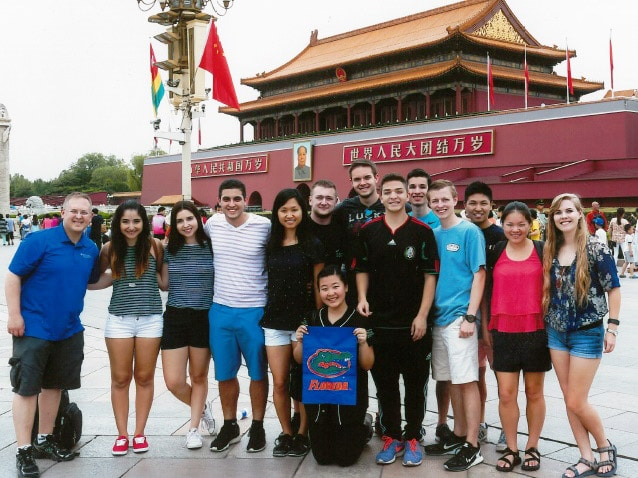 Jason Ward with students holding Florida Gator flag in the Forbidden City, in Beijing