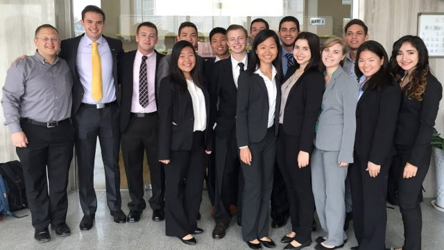 Jason Ward with students in business attire