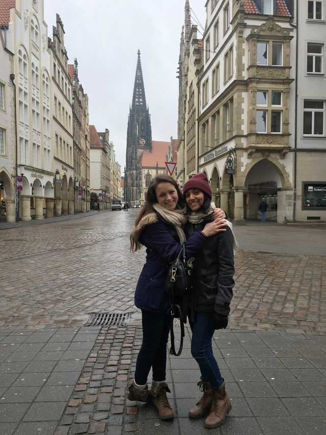 Two young women in Münster, Germany with St. Lambert's Church in the background