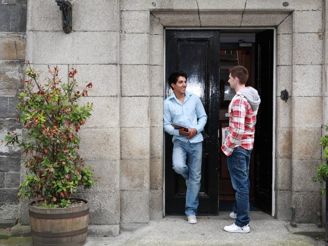 Two male students talking in the doorway of a building