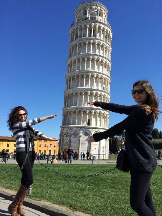 Two young women Gator Chomp with the Leaning Tower of Pisa in the background, Pisa, Italy