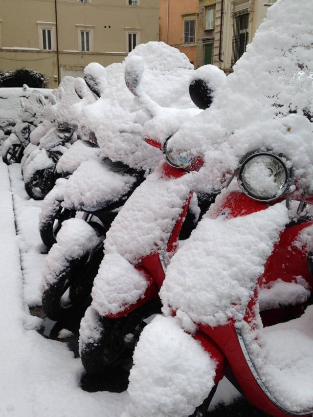 Scooters covered in snow line a street in Rome, Italy