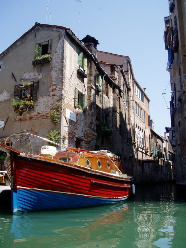 Red and blue boat docked along the watery streets of Venice, Italy