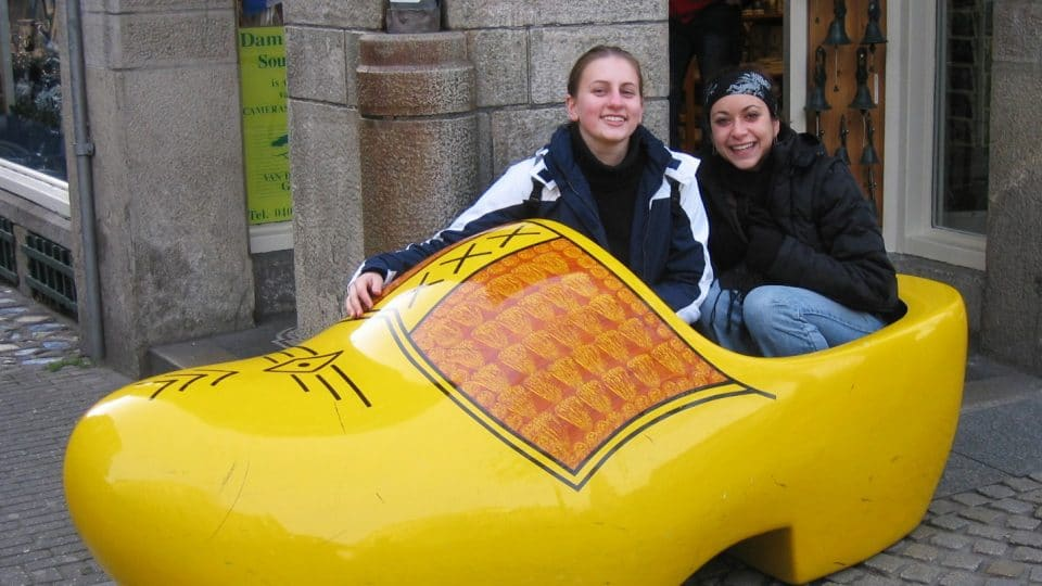 Two young women sit in a giant yellow clog in Amsterdam, Netherlands