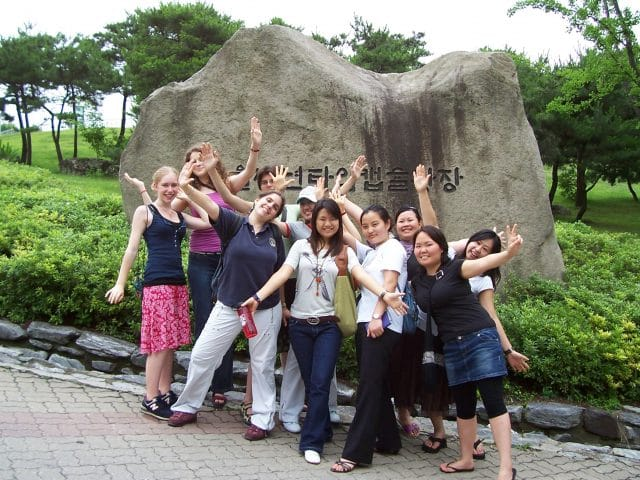 Students of different nationalities stand in from of a rock with writing on it in South Korea