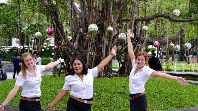 Three young women with a tree decorated in globes and other ornaments in the background