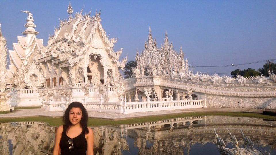Young woman stands before the White Temple in Thailand