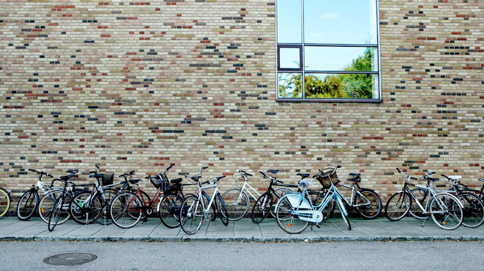 Bicycles parked along a building in Aarhus, Denmark