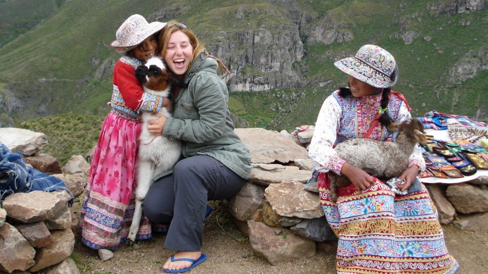 A local girl and a female international student hug a baby llama while another woman looks on in Machu Picchu, Peru