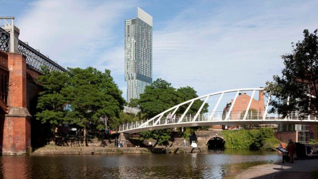 A skyrise with a walking bridge over water in Manchester, England