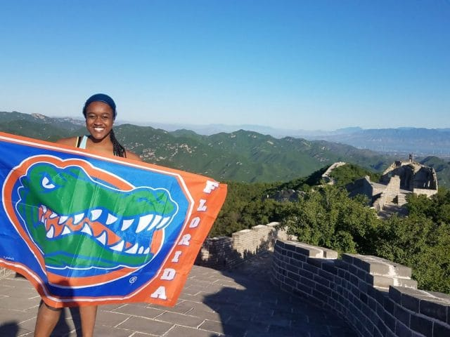 Student holds Gator flag with the Great Wall of China stretching out in the background