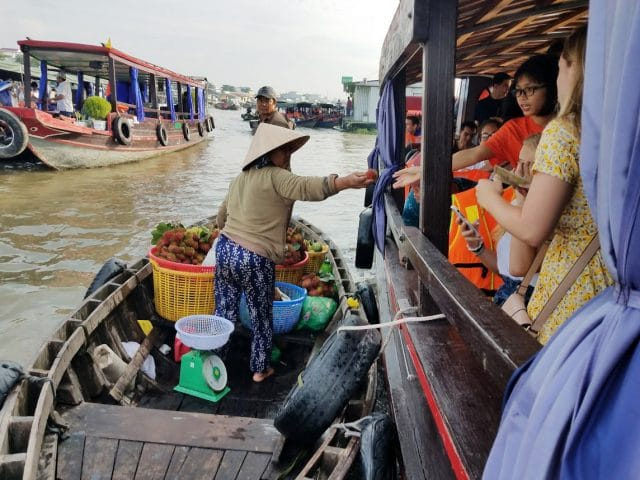 Woman selling produce from her boat at a floating market