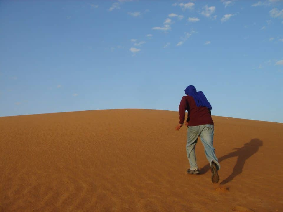 A young man runs up a sand dune in a Moroccan desert