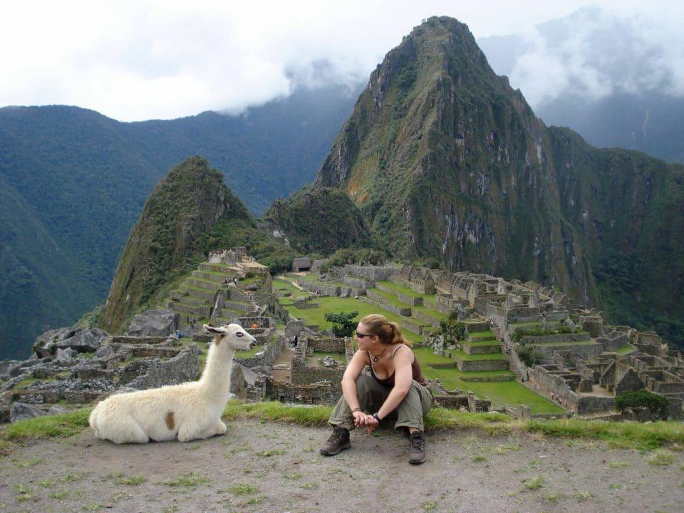 An alpaca and a young woman at Machu Picchu, Peru