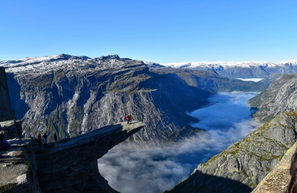 Student on cliff overlooking mountains and water in Norway