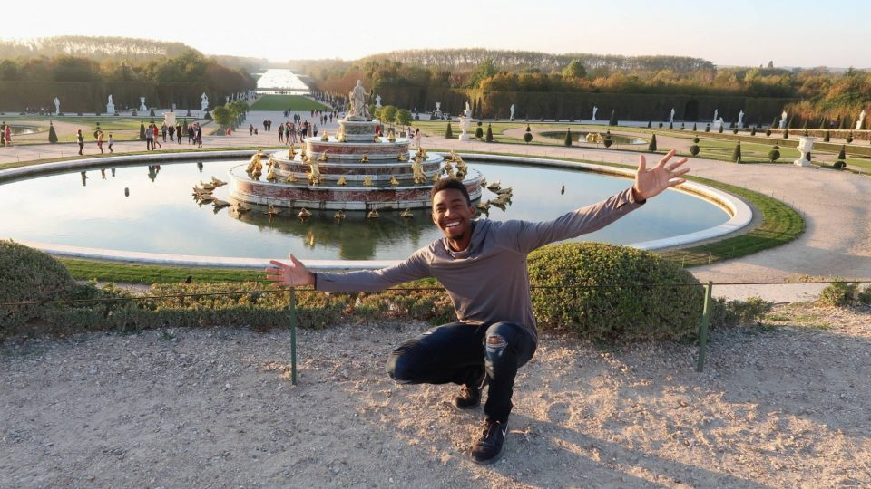 Student in front of fountain at Versailles Palace in Paris, France.