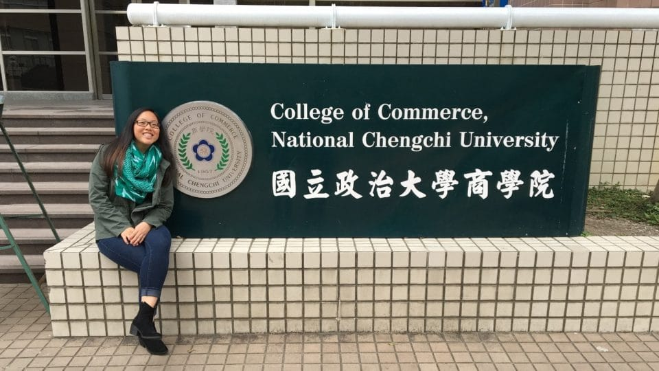 Student in front of the College of Commerce sign at National Chengchi University in Taiwan