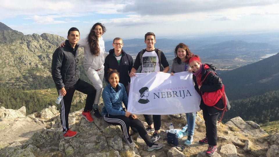 Student group holding sign at the top of Navacerrada Mountain Pass.