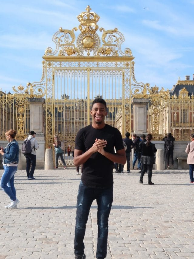 Student in front of gate at Versailles Palace in Paris, France.