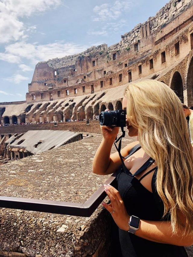 Student with binoculars inside the Colosseum in Rome, Italy.