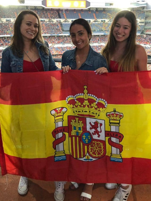 Three students holding flag of Spain in Bernabeu Stadium in Madrid, Spain.